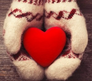 Hands in the mittens holding red heart